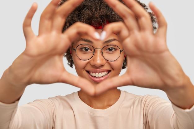 Foto de uma jovem atraente fazendo um gesto de formato de coração no rosto Foto gratuita