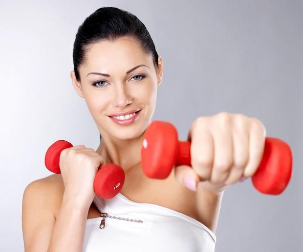 Foto de uma jovem de treinamento saudável com halteres. conceito de estilo de vida saudável. Foto gratuita