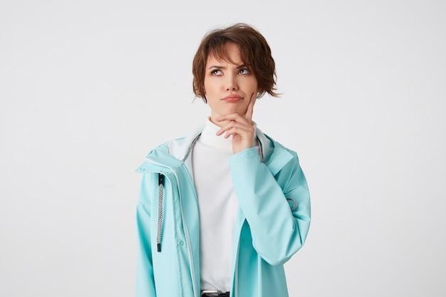 Foto de uma jovem senhora de cabelos curtos no golfe branco e casaco de chuva azul claro, toca a bochecha e carranca olha para cima, fica sobre um fundo branco. Foto gratuita