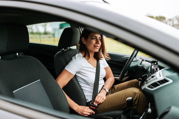 Foto de uma mulher de negócio que senta-se em um carro que põe sobre seu cinto de segurança. Foto Premium