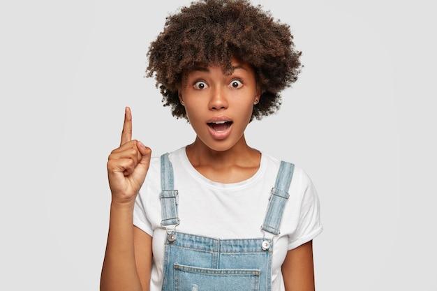 Foto de uma mulher emotiva de pele escura surpresa que prende a respiração, olha fixamente com olhos arregalados e levanta o dedo indicador Foto gratuita