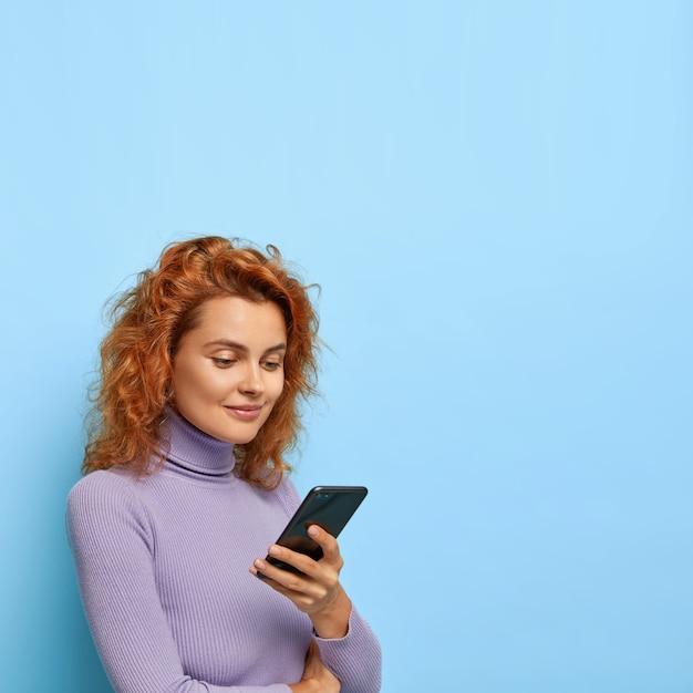 Foto de uma mulher ruiva de aparência agradável fica meio virada, usa smartphone moderno, verifica a caixa de e-mail, vestida com roupas casuais, isolada na parede azul, copia espaço para propaganda Foto gratuita