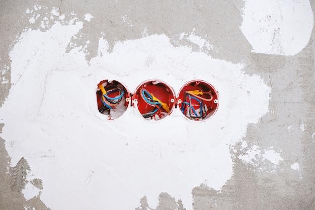 Foto de uma parede, com orifícios para caixas elétricas, processo de construção Foto Premium