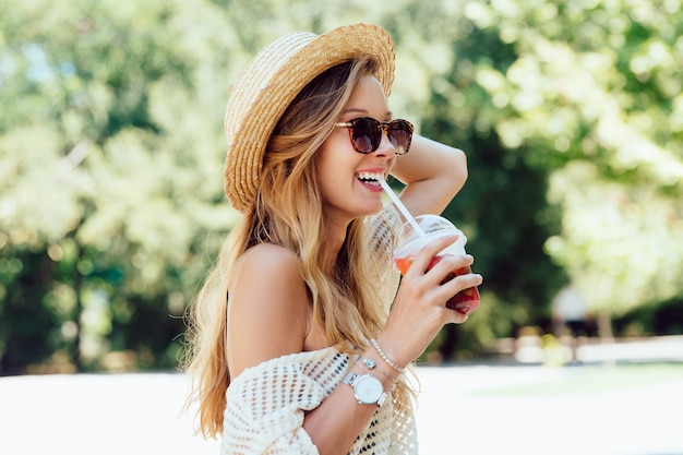 Foto de verão da linda mulher alegre em óculos de sol, beber um cocktail fresco de palha Foto gratuita