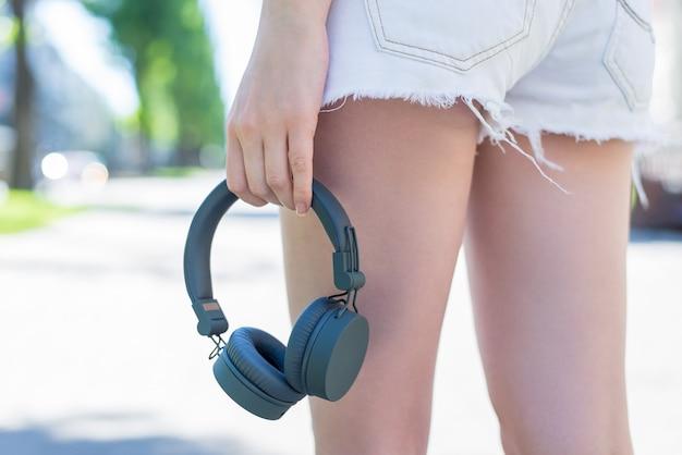 Foto de visão de baixo ângulo cortada de perto das pernas de uma senhora esportiva muito bonita e atraente em shorts jeans de brim branco, carregando fones de ouvido cinzentos da moda na mão Foto Premium