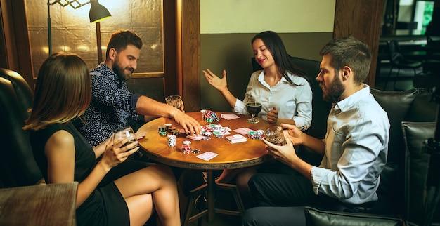 Foto de vista lateral de amigos masculinos e femininos, sentado à mesa de madeira. Foto gratuita