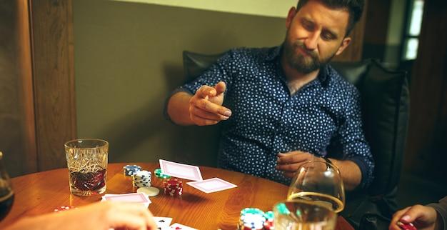 Foto de vista lateral de amigos sentados na mesa de madeira. amigos se divertindo enquanto jogava o jogo de tabuleiro. Foto gratuita