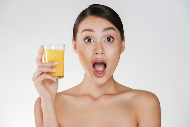 Foto divertida de mulher engraçada com cabelo escuro no coque, segurando um copo transparente de suco de laranja, isolado sobre a parede branca Foto gratuita