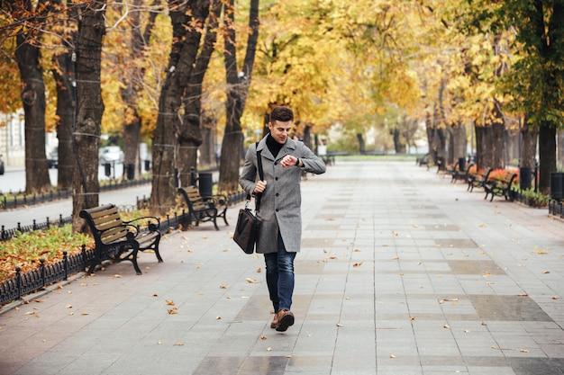 Foto do homem caucasiano bonito casaco com saco passeando no parque da cidade e olhando para o relógio Foto gratuita