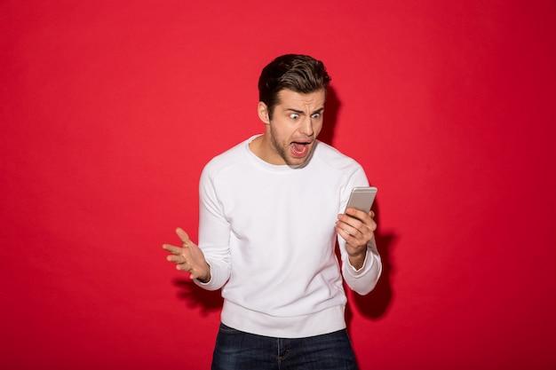 Foto do homem irritado na camisola que grita no smartphone sobre a parede vermelha Foto gratuita