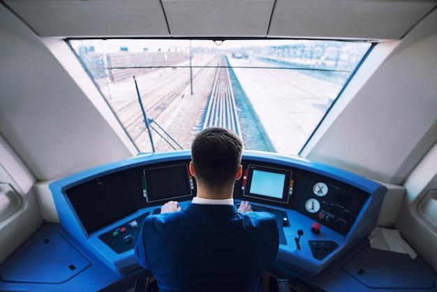 Foto do interior da cabine do trem com o maquinista sentado e dirigindo o trem Foto gratuita