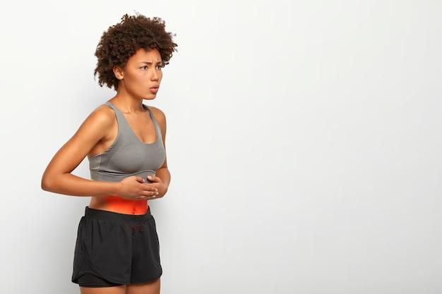 Foto do perfil de uma modelo afro-americana que sofre de dor de estômago, tem dor abdominal, toca a barriga, usa top e shorts, franze a testa por causa de sensações desagradáveis, poses contra um fundo branco Foto gratuita