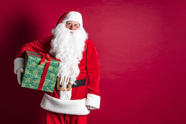 Foto do tipo papai noel dando presente de natal e olhando para a câmera Foto Premium