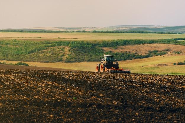Foto do trator cultivando uma terra, preparação para o ano novo. Foto Premium