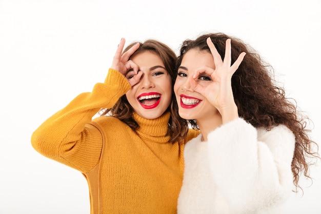 Foto - duas meninas felizes em camisolas se divertindo e mostrando gestos ok sobre parede branca Foto gratuita