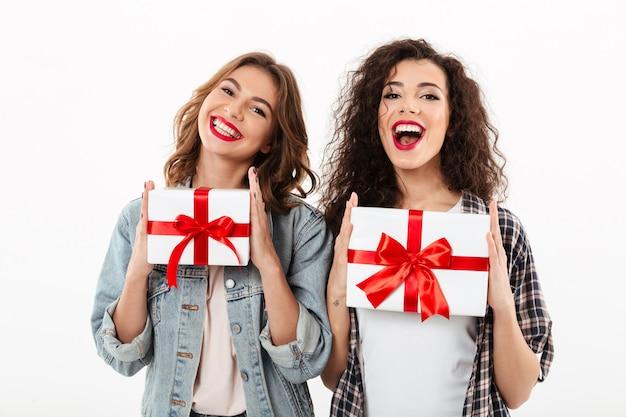 Foto - duas meninas felizes, segurando, presentes, em, mãos parede branca Foto gratuita