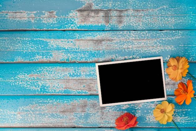 Foto em branco com flor em fundo de madeira azul velho Foto Premium