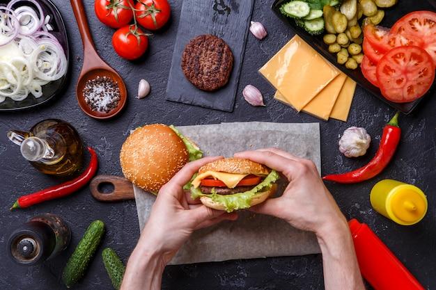 Foto em cima de dois hambúrgueres, mãos humanas, pimenta, Foto Premium