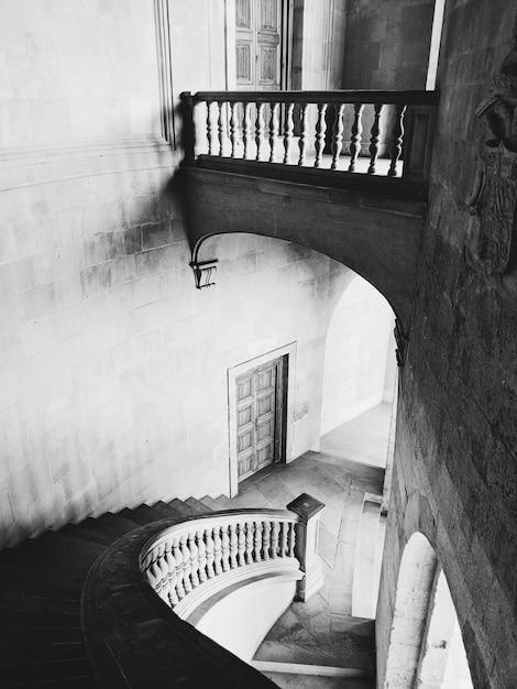 Foto em escala de cinza das escadas e corredores do palácio de alhambra em granada, espanha Foto gratuita