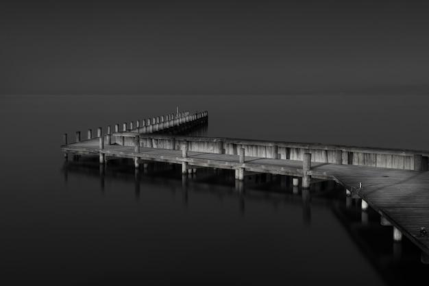 Foto em escala de cinza de um píer de madeira perto do mar durante o dia Foto gratuita