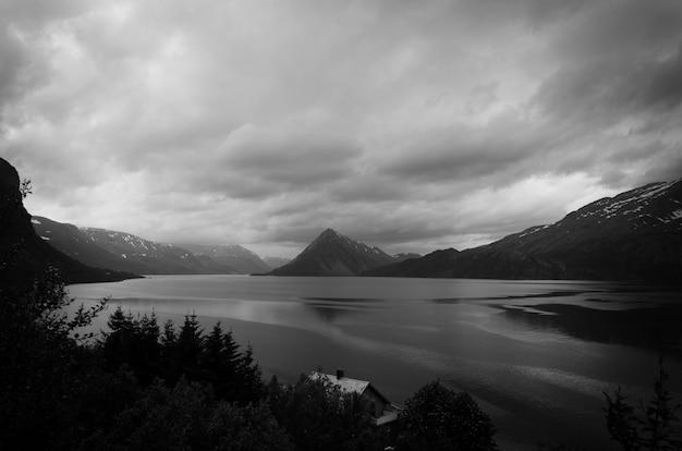 Foto em escala de cinza do lago cercado por montanhas e árvores Foto gratuita