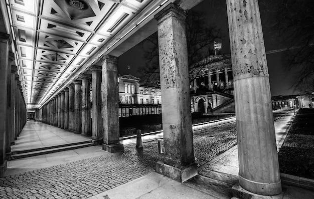 Foto em tons de cinza de um corredor com pilares Foto gratuita