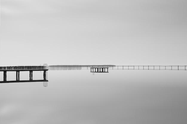 Foto em tons de cinza de um píer de madeira perto do mar sob um lindo céu nublado Foto gratuita