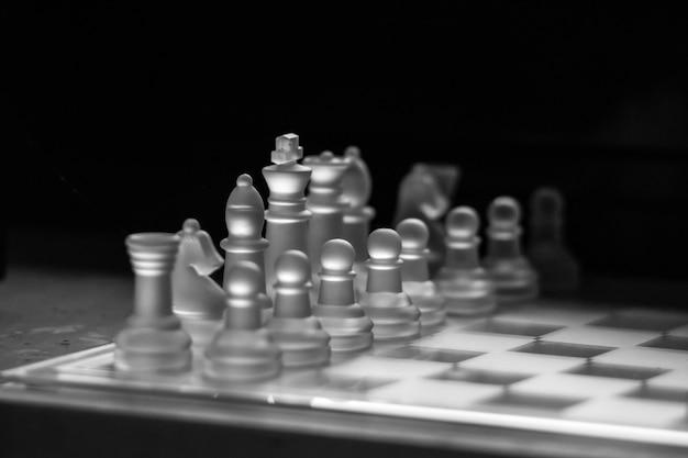 Foto em tons de cinza de um tabuleiro de xadrez de vidro Foto gratuita