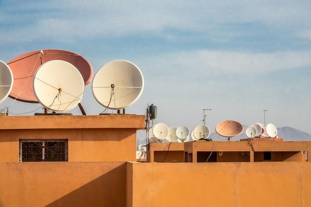 Foto grande angular de antenas parabólicas brancas no telhado de um edifício Foto gratuita