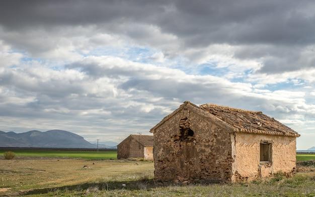 Foto grande angular de casas antigas em um campo verde sob um céu nublado Foto gratuita