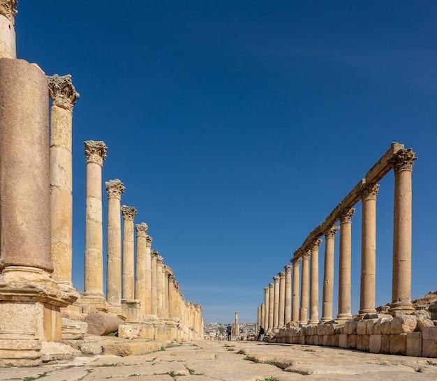 Foto grande angular de uma construção antiga com torres na jordânia sob um céu azul claro Foto gratuita