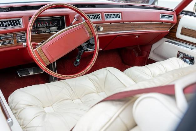 Foto grande angular do interior de um carro, incluindo o volante vermelho e os bancos brancos Foto gratuita