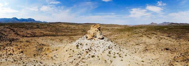 Foto grande angular do vale arenoso com uma rocha no meio Foto gratuita
