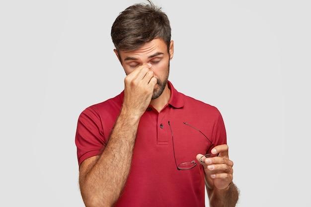 Foto horizontal de um cara bonito sobrecarregado mantém a mão no nariz, tira os óculos, sente dor nos olhos depois do trabalho no computador, quer dormir, usa uma camiseta vermelha casual, isolado sobre a parede branca Foto gratuita