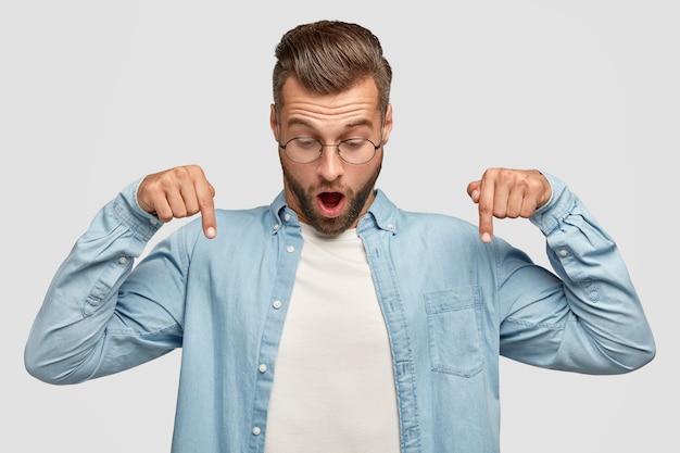 Foto horizontal de um jovem com barba por fazer surpreso aponta para baixo, abre a boca amplamente, vê algo impressionante no chão, usa uma camisa elegante, isolada sobre uma parede branca. conceito de pessoas e emoções Foto gratuita