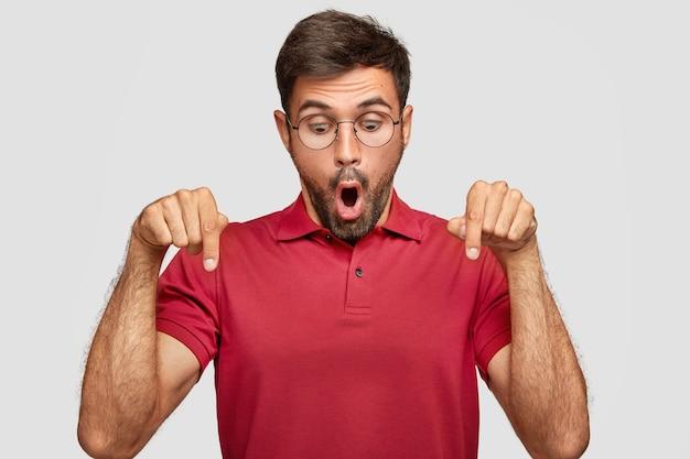 Foto horizontal de um jovem estupefato parece surpreendentemente e indica para baixo, sendo atordoado por algo inacreditável, usa uma camiseta vermelha brilhante casual, fica contra uma parede branca Foto gratuita