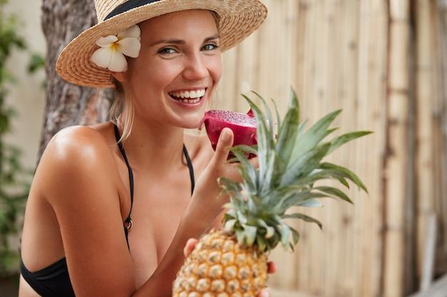 Foto horizontal de uma linda mulher sorridente com um largo sorriso brilhante, usa chapéu de verão e maiô, segura frutas tropicais, desfruta de um inesquecível descanso de verão, passa momentos de lazer nos trópicos Foto gratuita