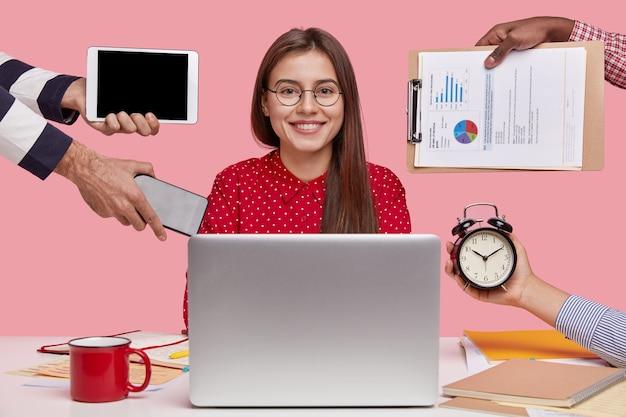 Foto horizontal de uma linda mulher sorridente de camisa vermelha sentada em frente a um laptop aberto Foto gratuita