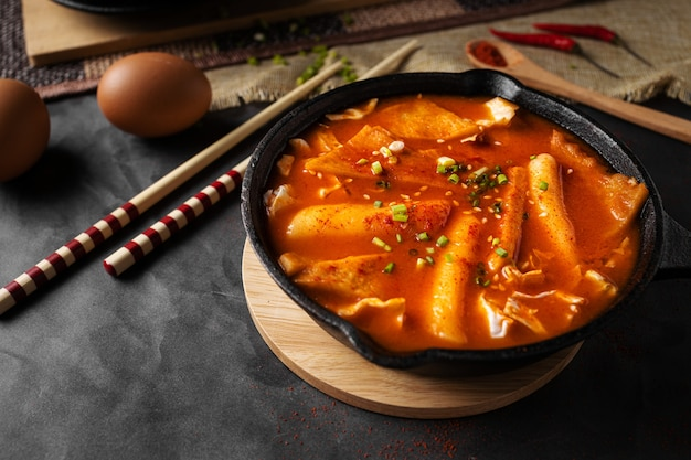Foto horizontal de uma sopa em uma tigela preta e alguns ovos e pauzinhos de madeira Foto gratuita