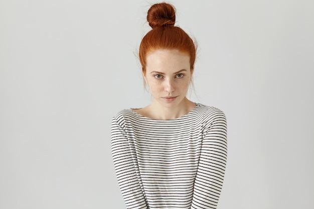 Foto interior da ruiva bonita com nó de cabelo, vestindo camiseta de mangas compridas listrada casual, sua postura expressando timidez. bela jovem posando na parede em branco Foto gratuita