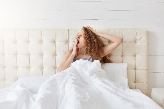 Foto interior de pacífica jovem atraente relaxante na cama na manhã Foto gratuita