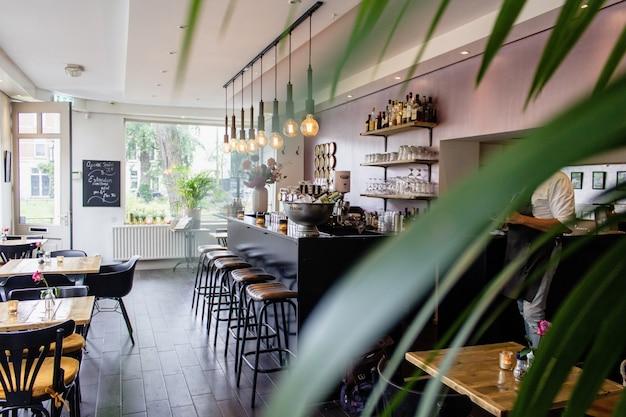 Foto interior de um café com cadeiras perto do bar com mesas de madeira Foto gratuita