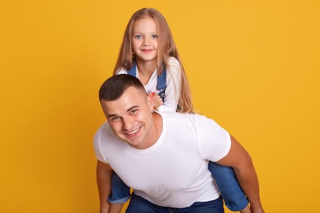 Foto interior do alegre pai dando cavalinho para sua filha contra amarelo, feliz família vestindo roupas casuais Foto gratuita