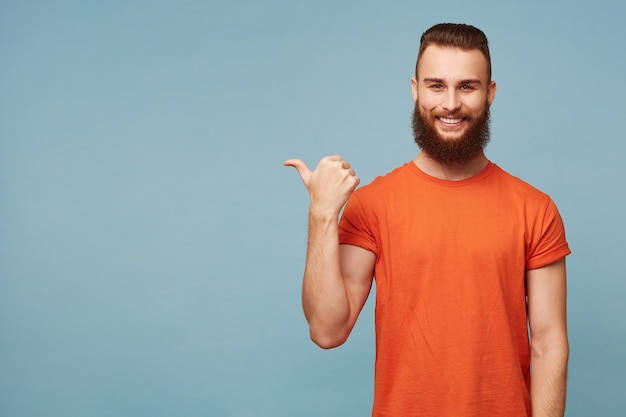 Foto interna de um cara barbudo bonito feliz encantado em azul Foto gratuita
