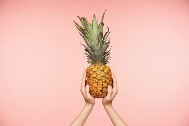 Foto interna de um delicioso abacaxi fresco sendo segurado pelas mãos de pele clara de mulheres bonitas sendo levantadas enquanto posava sobre um fundo rosa. conceito de alimentos e frutas frescas Foto gratuita