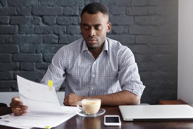 Foto interna de um financeiro afro-americano sério estudando documentos financeiros durante o intervalo para o café em um café Foto gratuita