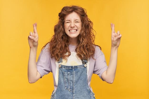 Foto interna de uma jovem estudante usando macacão jeans azul e camiseta roxa, cruzou os dedos em posição de oração, esperando um bom resultado nos exames. isolado sobre a parede amarela Foto gratuita