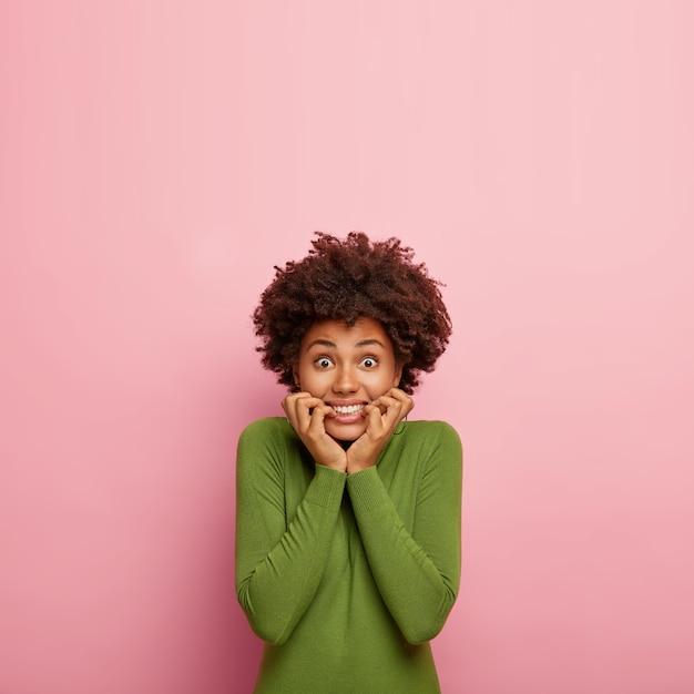 Foto interna de uma jovem modelo morde as unhas nervosamente, com os olhos bem abertos, receia de algo horrível na vida, vestida com um macacão verde, isolada na parede rosa com espaço de cópia Foto gratuita