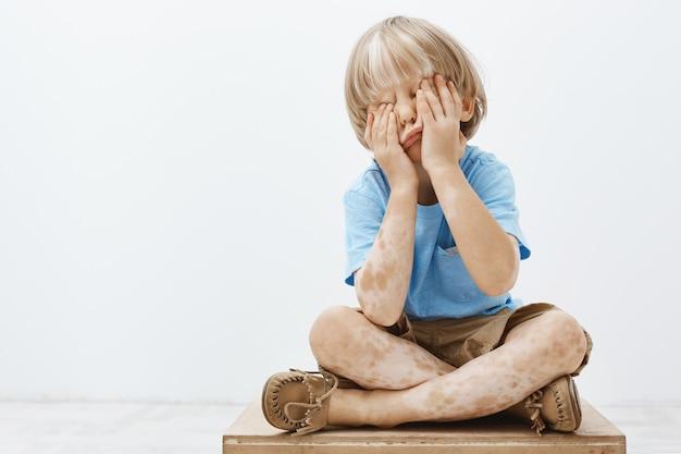 Foto interna de uma linda criança europeia com um lindo corte de cabelo e vitiligo, cobrindo o rosto com as palmas das mãos enquanto está sentado, brincando de esconde-esconde com o irmão mais velho Foto gratuita