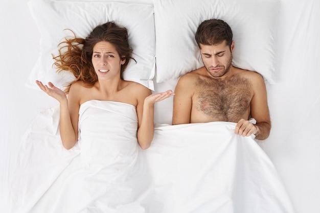 Foto interna de uma mulher chateada na cama, encolhendo os ombros em confusão, preocupada com o marido que está sofrendo de impotência Foto gratuita